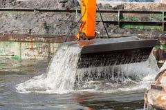 Ковш экскаватора выкапывая в песке от воды Стоковые Изображения