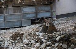 Ковш экскаватора лежит в хламе сокрушенного здания, d Стоковая Фотография RF