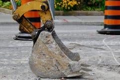 Ковш экскаватора сидит бесполезное на дороге Стоковые Изображения