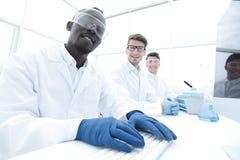 Когорта ученых сидя на таблице лаборатории стоковое фото rf