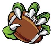 Коготь изверга животный держа шарик американского футбола бесплатная иллюстрация