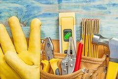 Кожаное toolbelt с tooling конструкции на деревянной верхней части доски соперничает Стоковая Фотография RF