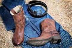 Кожаные ботинки ковбоя кожаный пояс и джинсы на соломе Стоковое Фото