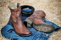 Кожаные ботинки ковбоя кожаный пояс и джинсы на соломе Стоковые Фотографии RF