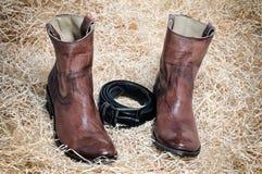 Кожаные ботинки ковбоя кожаный пояс и джинсы на соломе Стоковые Фото