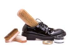 Кожаные ботинки с комплектом для обслуживания ботинка на белой предпосылке стоковое фото