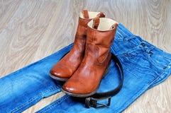 Кожаные коричневые ботинки и пояс ковбоя на голубых джинсах Стоковая Фотография