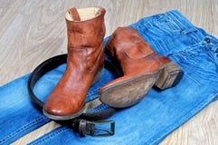 Кожаные коричневые ботинки и пояс ковбоя на голубых джинсах Стоковое Изображение RF