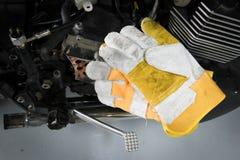 Кожаные перчатки безопасности на двигателе мотоцикла подготавливают обслуживать стоковые фото