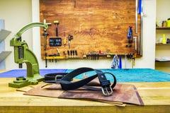Кожаные пояс и сжатия мастерской на таблице Стоковая Фотография