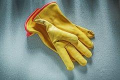 Кожаные работая перчатки на конкретном conce конструкции предпосылки Стоковые Фото