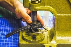 Кожаный мастер мастерской сжимает пояс для того чтобы ввести пряжку Стоковое Фото