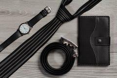 Кожаный пояс, вахта, silk связь, тетрадь на сером деревянном backgro Стоковые Фотографии RF