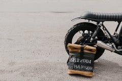 Кожаный рюкзак около мотоцикла Наполовину черный мотоцикл в гараже Kaferacers мотоцикла Стоковое Изображение