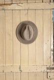 Кожаный шлем ковбоя вися на старой двери Стоковая Фотография RF