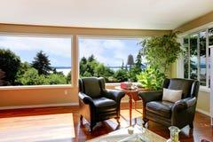 2 кожаных кресла для отдыха и больших окна в угле жить Стоковая Фотография