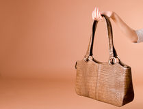кожа удерживания сумки руки предпосылки бежевая Стоковое Изображение