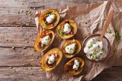 Кожи картошки с сыром, беконом и сметаной на таблице Hor Стоковые Фотографии RF
