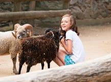 Козы craddle девушки в ферме Стоковые Изображения RF