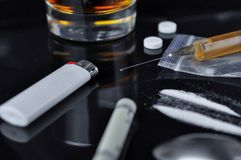 Кокаин, пилюльки, спирт и героин в шприце стоковое фото