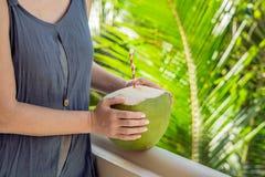 Кокос в красивых женских руках на зеленой предпосылке Преимущества концепции воды кокоса Стоковое Фото