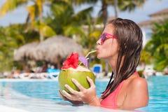 Кокос красивой женщины выпивая бассейном Стоковая Фотография