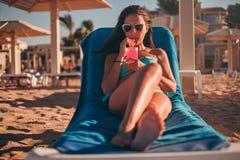 Коктеиль брюнет выпивая и слушая музыка на пляже стоковые фото