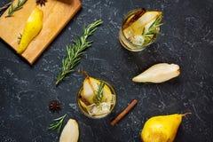 Коктеиль груши с ромом, ликером, кусками груши и розмариновым маслом на черной каменной таблице, селективным фокусом Стоковая Фотография RF