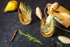 Коктеиль груши с ромом, ликером, кусками груши и розмариновым маслом на черной каменной таблице Стоковое Фото
