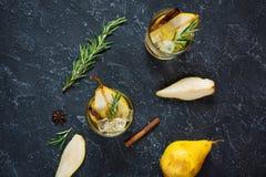 Коктеиль груши с ромом, ликером, кусками груши и розмариновым маслом на черной каменной таблице, селективным фокусом Стоковые Изображения RF