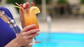 Коктеиль девушки выпивая от соломы рядом с бассейном сток-видео
