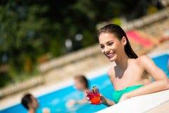 Коктеиль красивой женщины выпивая на бассейне стоковая фотография rf