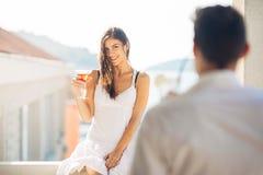Коктеиль привлекательной женщины выпивая и наслаждаться ее летними каникулами Выпивая освежающий напиток и усмехаться к человеку Стоковые Фото