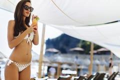 Коктеиль сногсшибательной женщины выпивая на пляже Стоковое фото RF