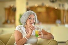 Коктеиль старшей женщины выпивая Стоковые Изображения RF