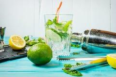 Коктеиль Mojito с известкой и мятой в стекле highball на голубой деревянной таблице Питье делая инструменты и ингридиенты для кок Стоковое Изображение