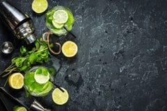Коктеиль Mojito с известкой и мятой в стекле highball на каменной таблице Питье делая инструменты и ингридиенты Скопируйте космос Стоковые Фото