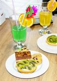 2 коктеиля, зеленый цвет, желтый цвет, оранжевые трубки украшения, торт с Стоковое Изображение RF