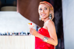 Коктеили азиатской женщины выпивая в причудливом баре Стоковое Изображение RF