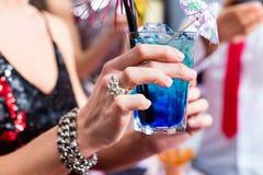 Коктеили женщины выпивая в коктейль-баре Стоковые Изображения