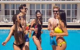 Коктеили и пиво людей выпивая во время партии на бассейне Стоковая Фотография RF