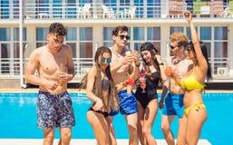 Коктеили и пиво людей выпивая во время партии на бассейне Стоковое Изображение RF