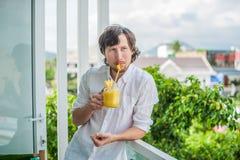 Коктеиль ананаса с куском в человека рук на террасе Тропическая принципиальная схема Стоковое Изображение RF