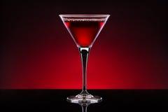 Коктеиль вишни в кристаллическом стекле изолированном на красном черном backgro Стоковая Фотография