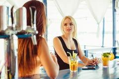 Коктеиль в руке женщины на открытой террасе в баре во время временени Стоковые Фотографии RF