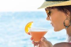 Коктеиль девушки выпивая на море Стоковые Изображения