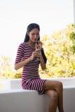 Коктеиль женщины выпивая пока сидящ на подпорной стенке Стоковое фото RF