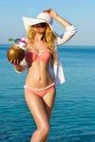 Коктеиль кокоса молодой женщины выпивая на пляже Стоковые Изображения