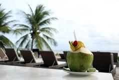 Коктеиль кокоса на таблице с запачканной предпосылкой Стоковые Фото