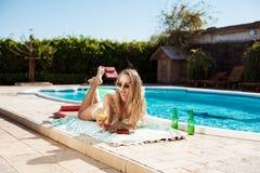 Коктеиль красивой белокурой девушки выпивая, загорать, лежа около бассейна Стоковое фото RF
